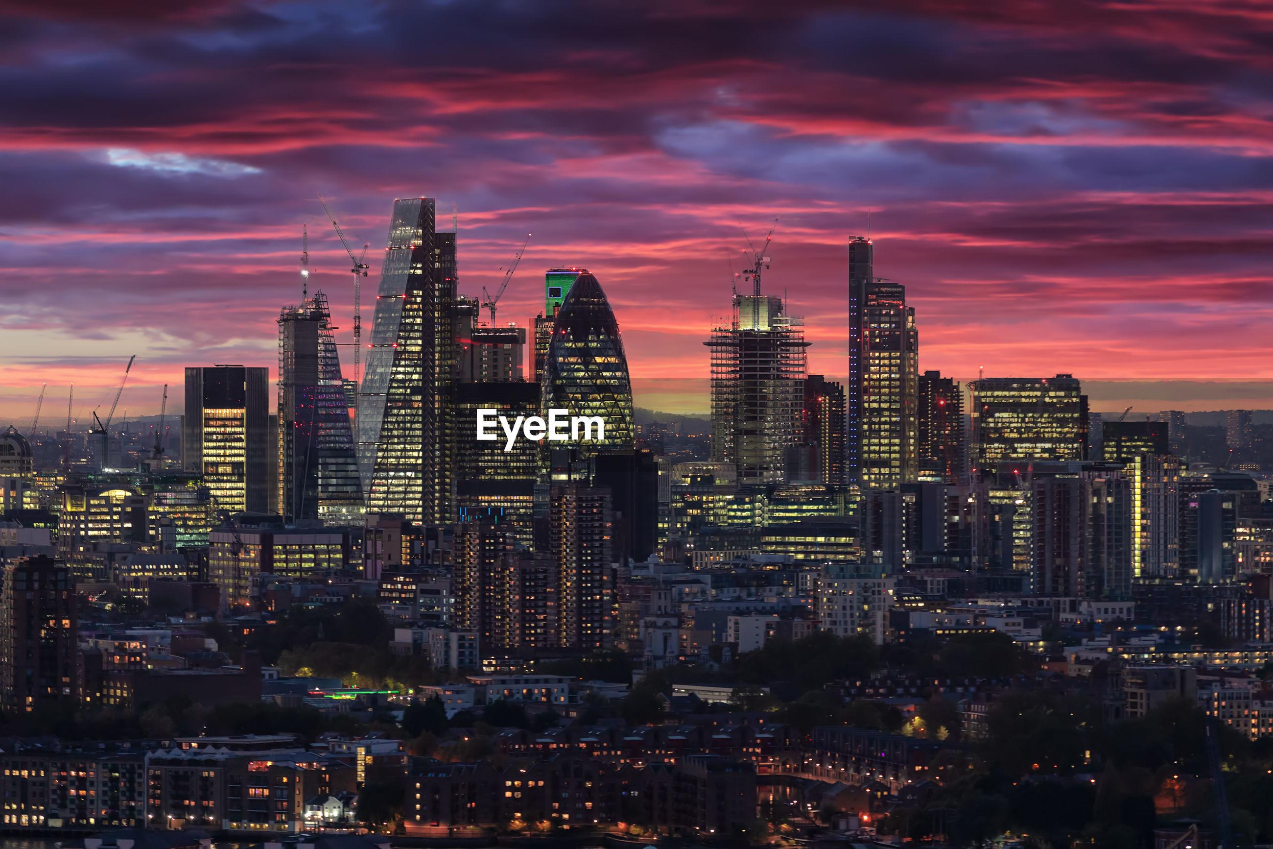 Illuminated cityscape against sky during sunset