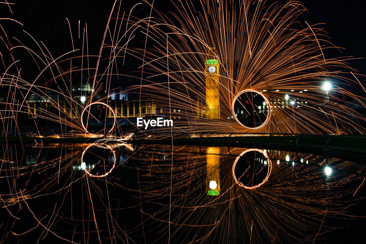 night, illuminated, motion, long exposure, blurred motion, speed, water, glowing, no people, architecture, light trail, wire wool, nature, built structure, outdoors, transportation, light - natural phenomenon, reflection, city, sparks, firework, firework display, light