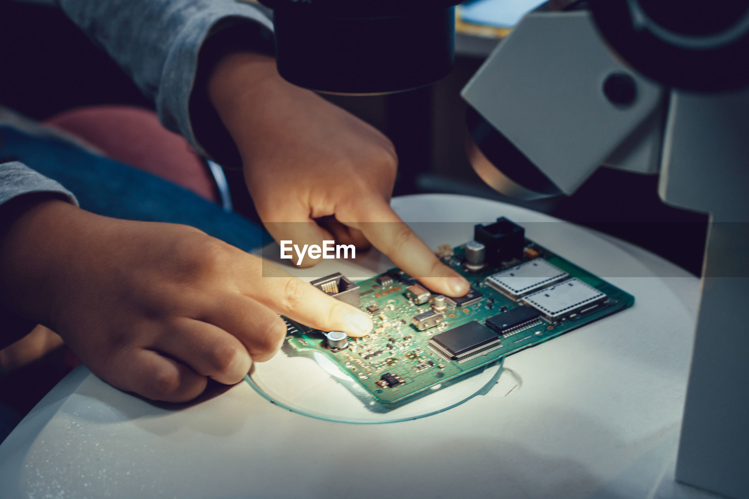 Cropped image of technician adjusting circuit board on microscope slide indoors