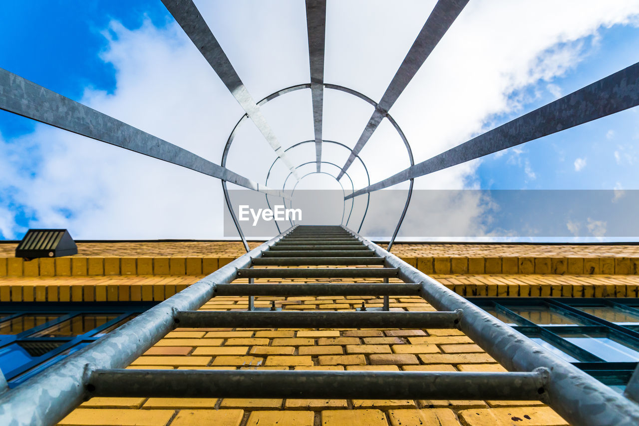 Directly below shot of covered ladder on building against cloudy sky