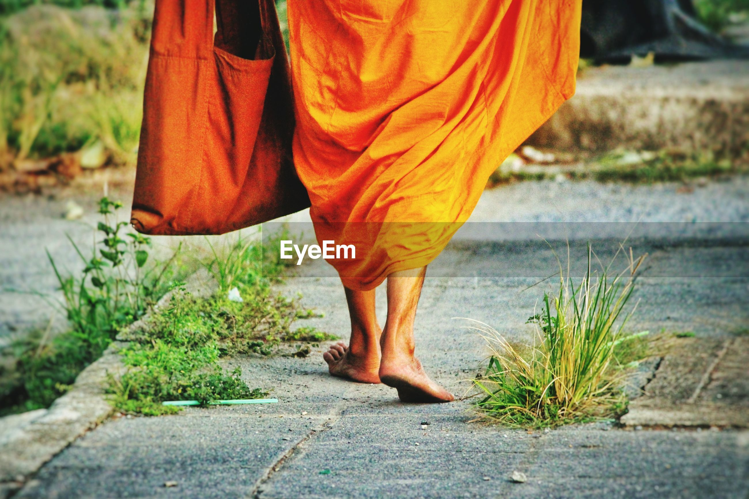 Low section of monk walking on footpath