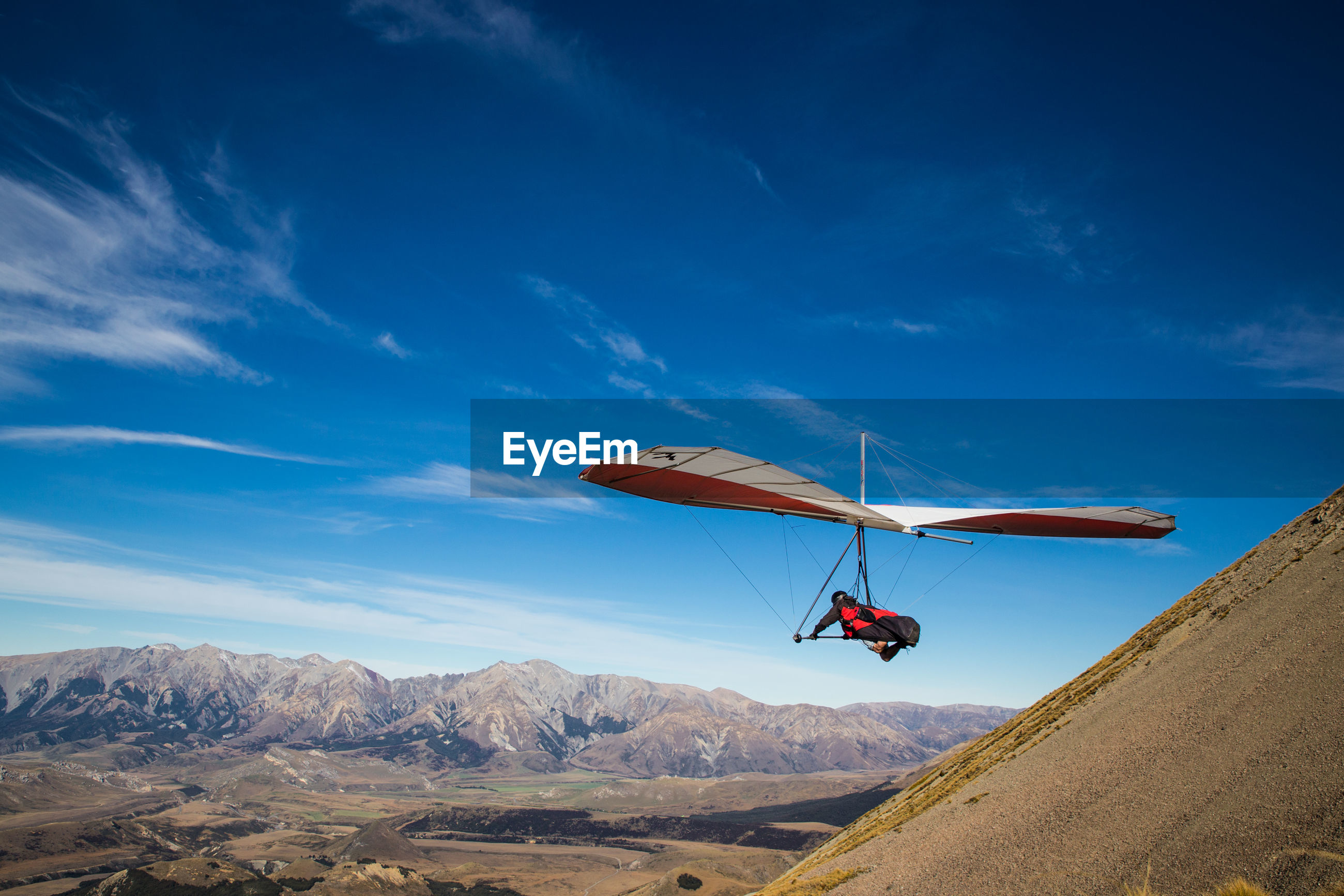 LOW ANGLE VIEW OF HELICOPTER FLYING IN MOUNTAINS AGAINST SKY