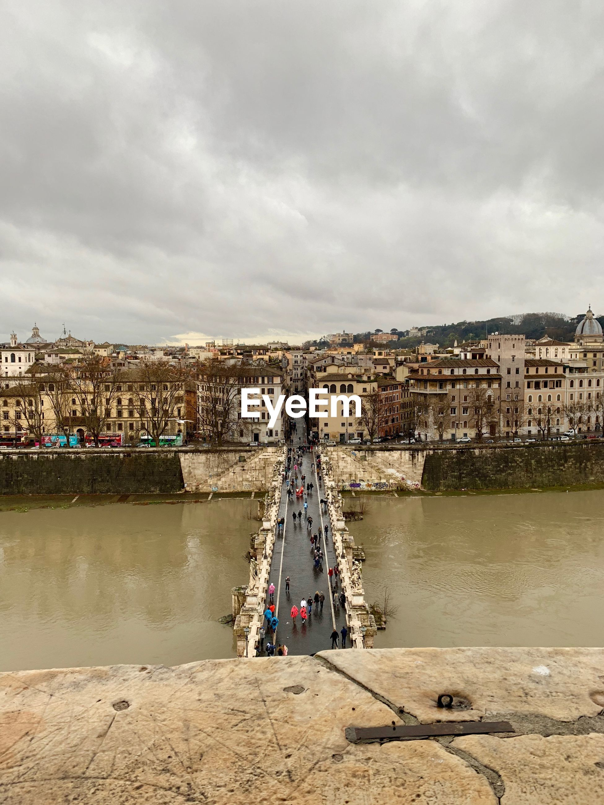High angle view of people on bridge over river by cityscape against cloudy sky