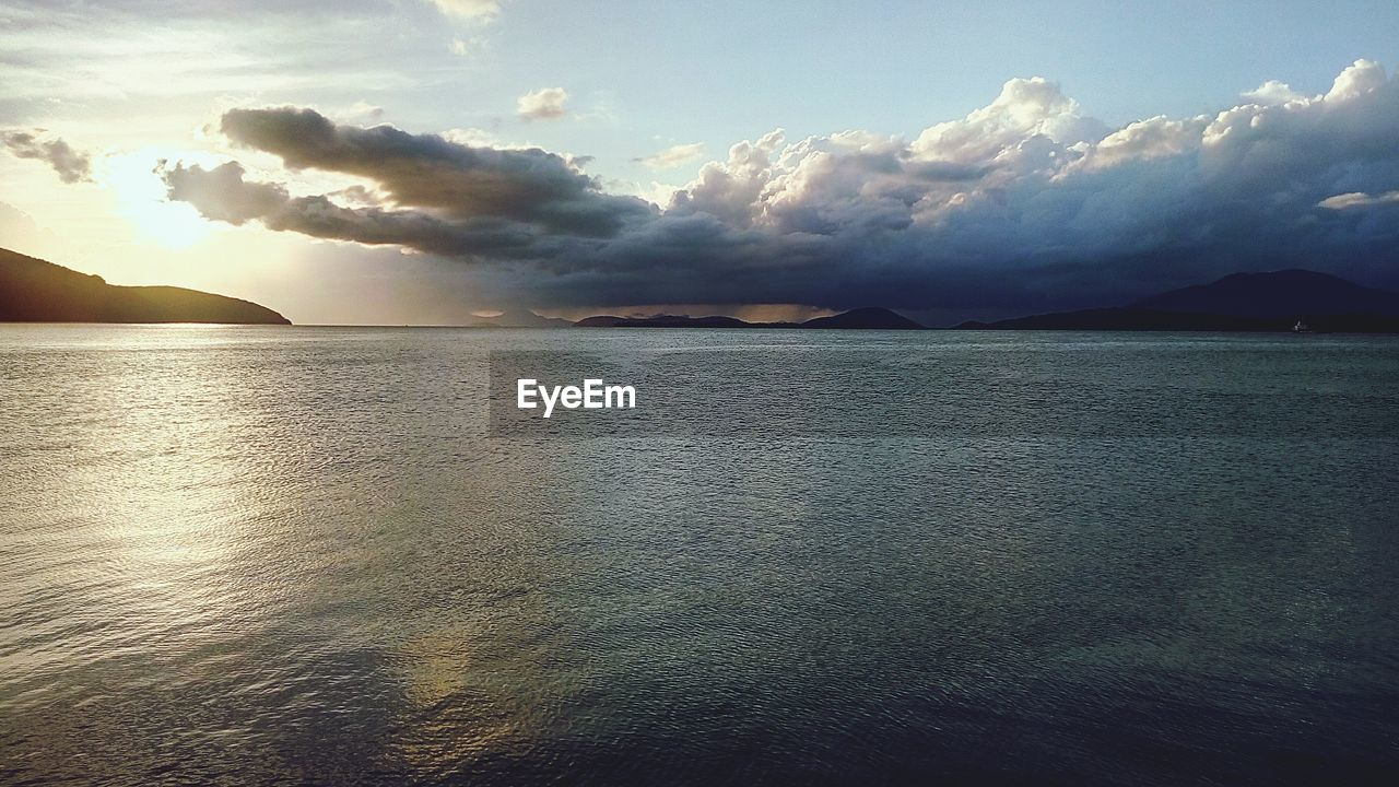 scenics, sky, beauty in nature, tranquility, sea, nature, tranquil scene, cloud - sky, water, sunset, no people, mountain, outdoors, waterfront, day, horizon over water