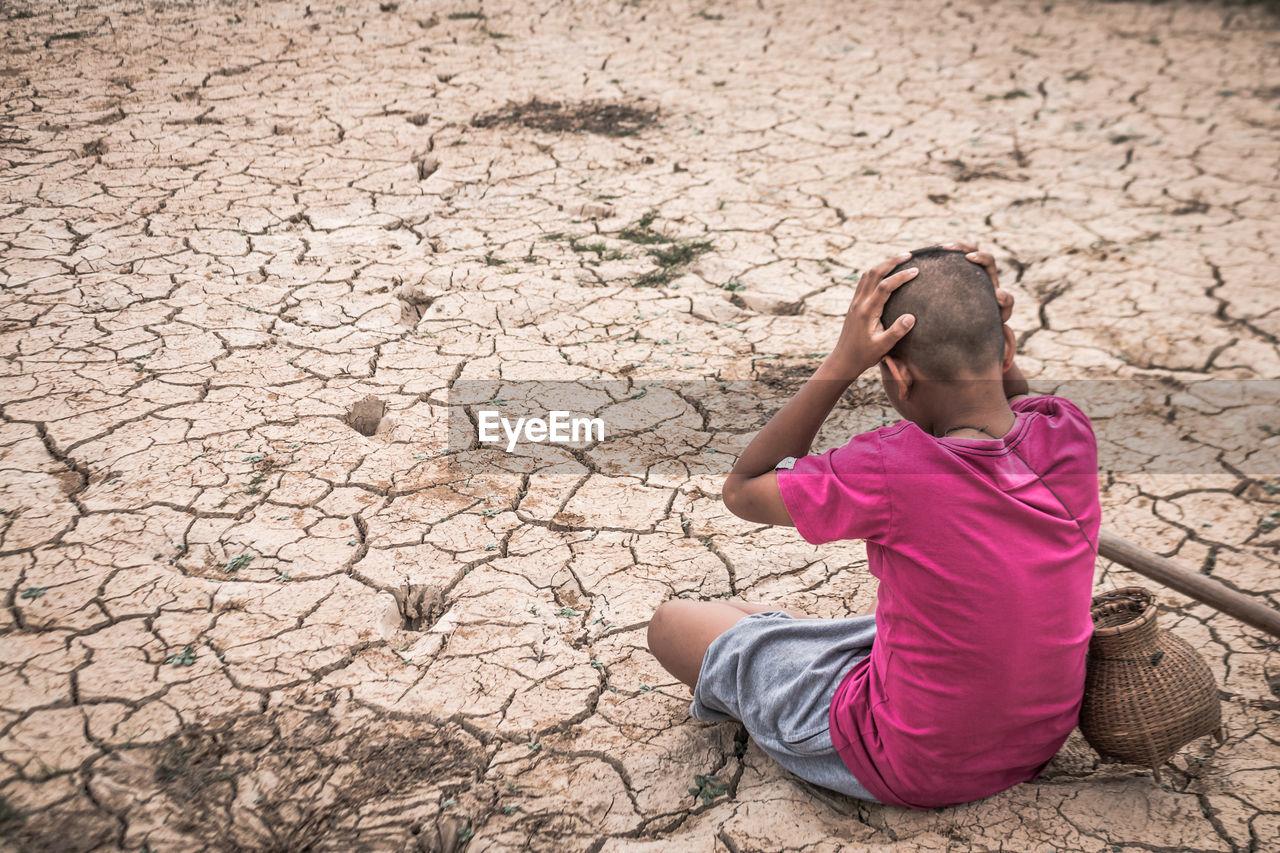 Rear View Of Boy Sitting On Barren Field