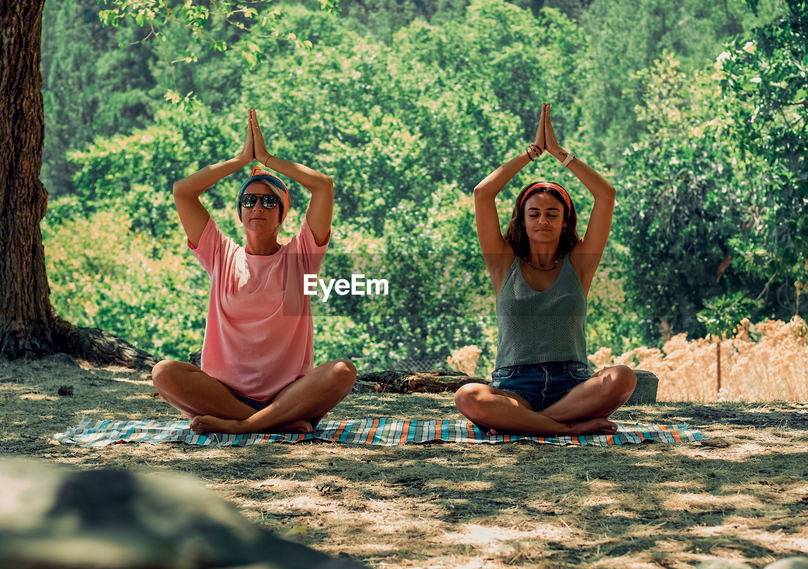 Two women doing yoga exercises in the nature. adults sitting in lotus position.