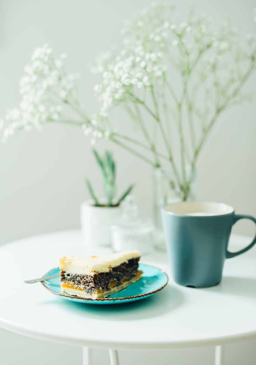 Cake By Coffee Cup In Plate On Table