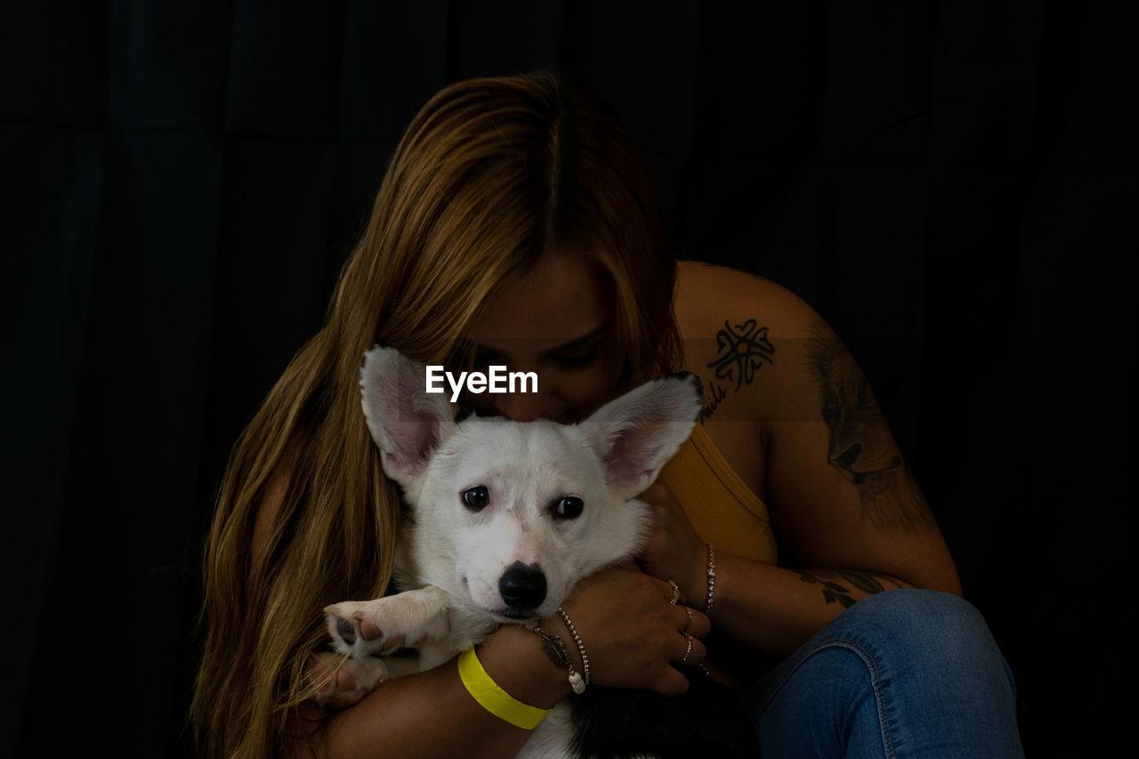 Woman kissing dog against black background