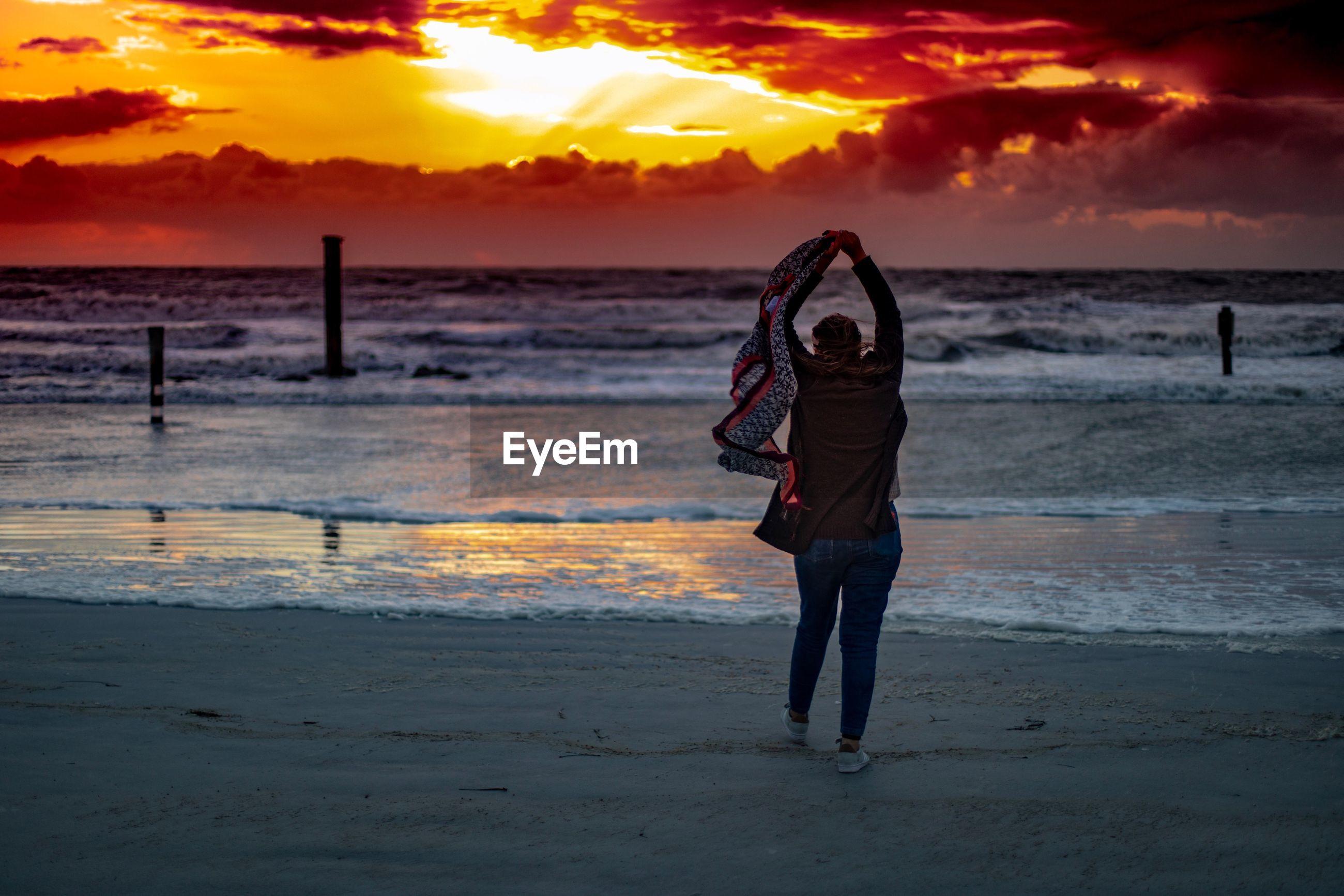 FULL LENGTH OF MAN STANDING ON BEACH AGAINST SKY DURING SUNSET