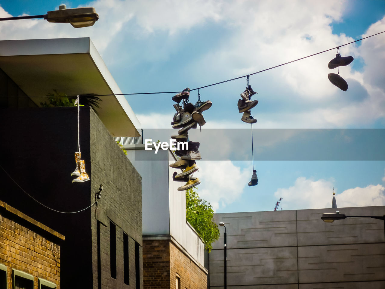 architecture, building exterior, sky, built structure, low angle view, cloud - sky, hanging, building, nature, no people, lighting equipment, day, city, residential district, outdoors, cable, sunlight, roof, shoe, decoration