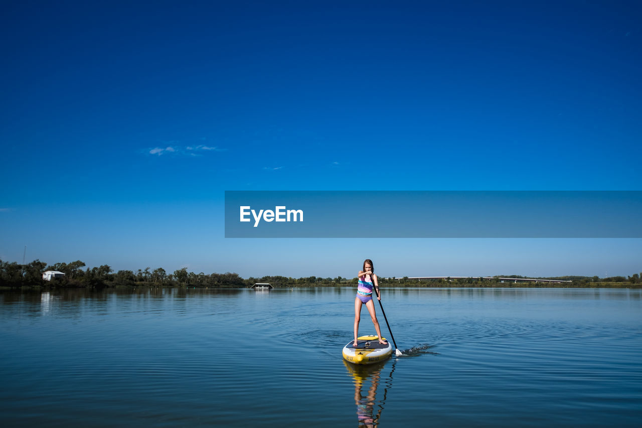 MAN ON BOAT IN LAKE AGAINST SKY