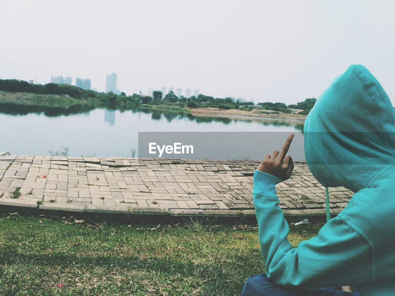 Man showing middle finger by lake