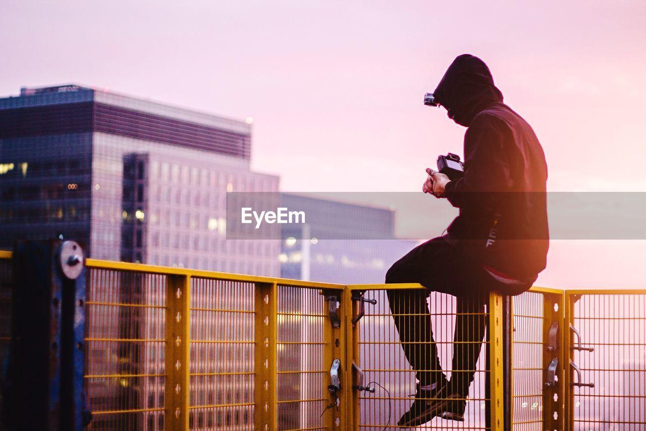 Man Sitting On Railing With Camera During Sunrise