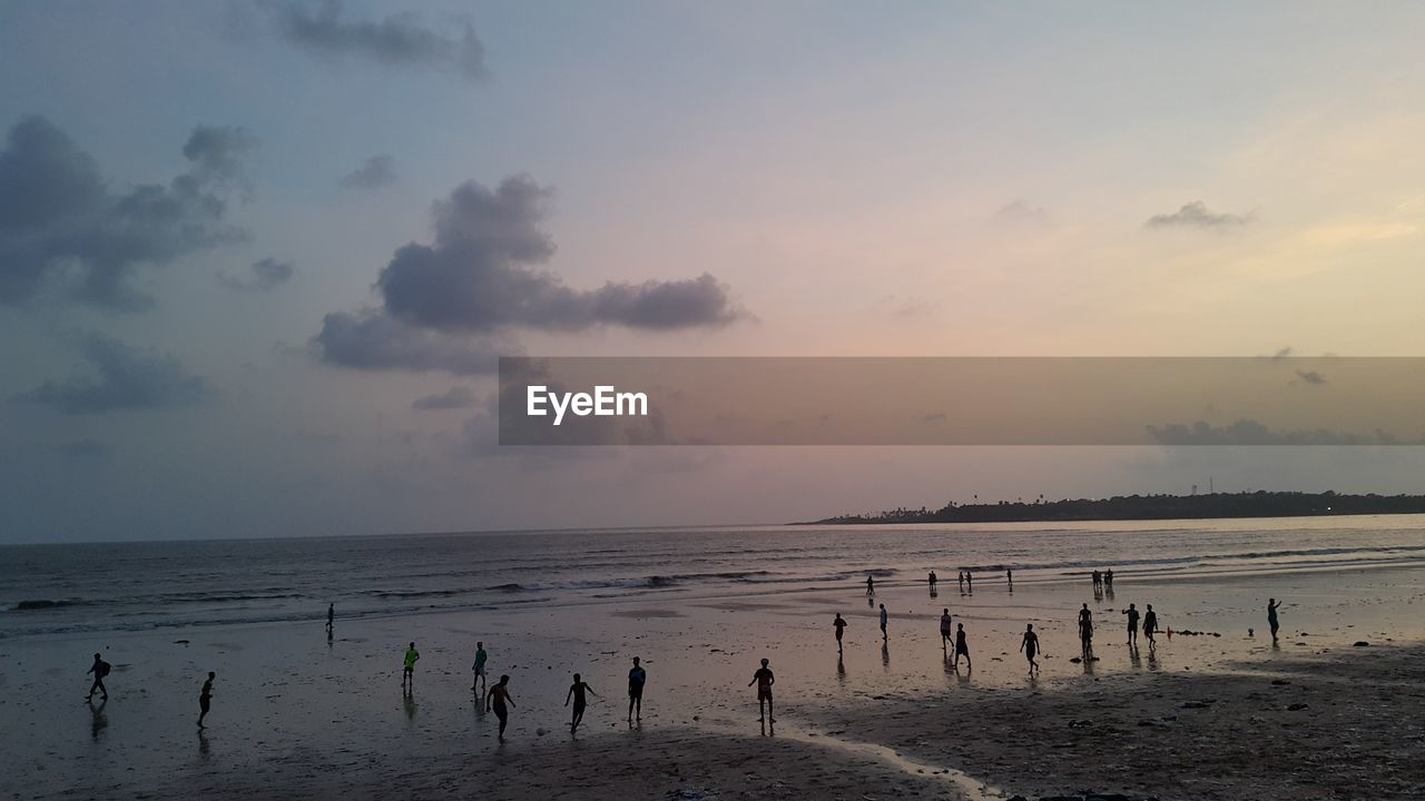 sky, sea, beach, water, land, beauty in nature, horizon, horizon over water, cloud - sky, scenics - nature, sunset, nature, tranquility, real people, group of people, non-urban scene, tranquil scene, large group of people, holiday, outdoors, wooden post