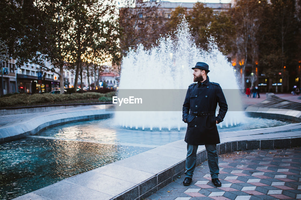 one person, water, real people, architecture, full length, lifestyles, fountain, men, tree, young adult, leisure activity, motion, standing, day, nature, city, young men, plant, outdoors, warm clothing, teenager