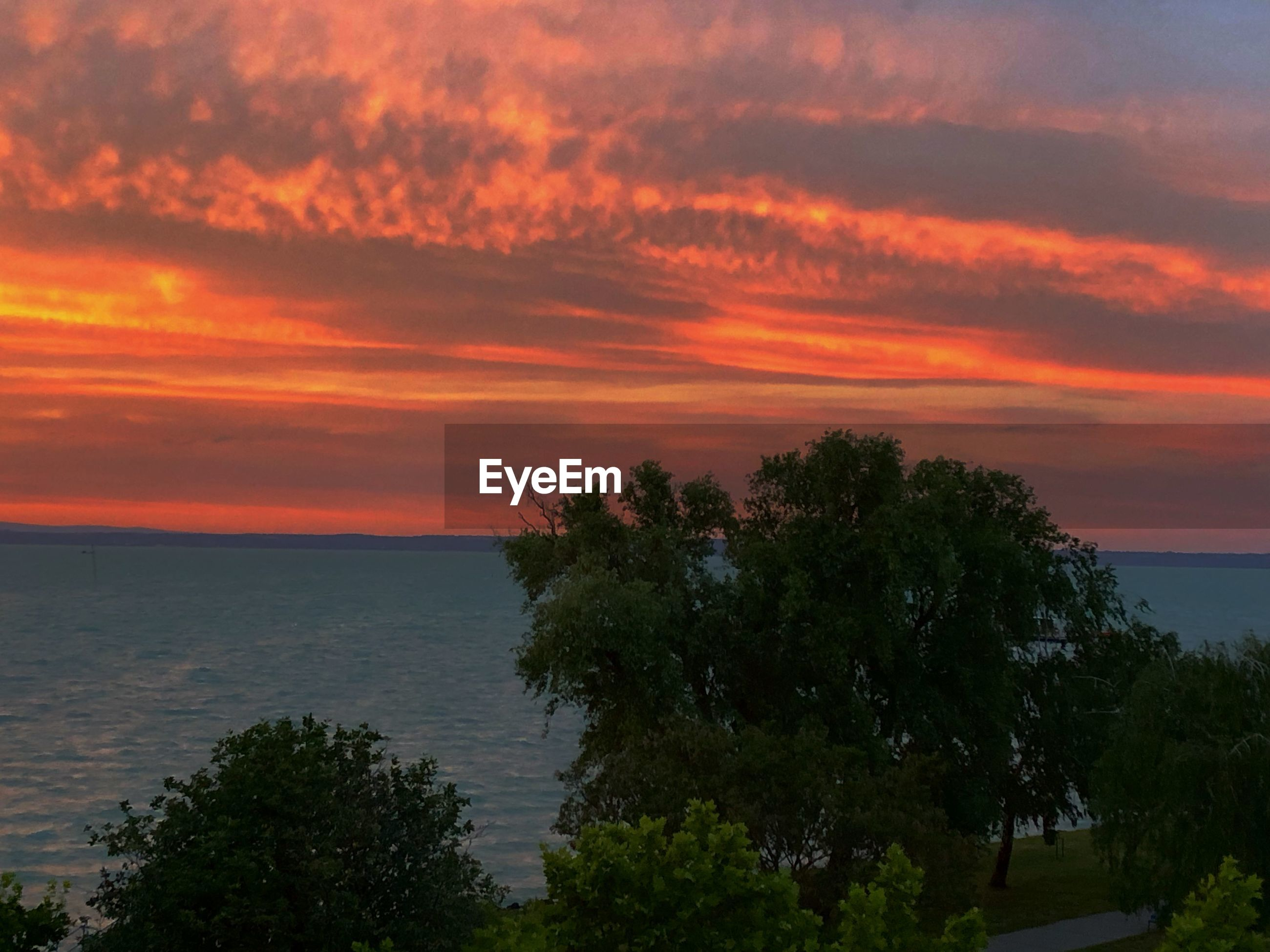 SCENIC VIEW OF SEA AGAINST ORANGE SUNSET SKY