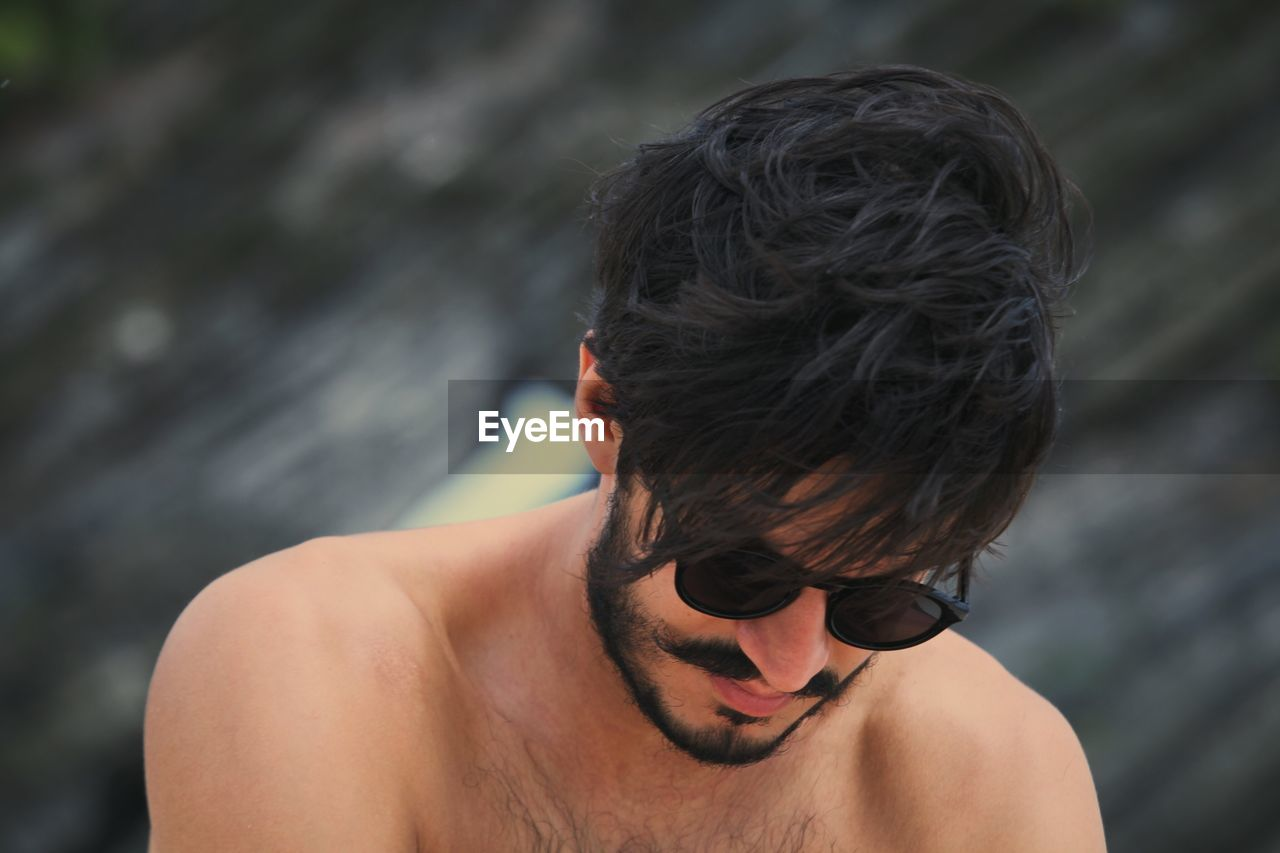 Close-Up Of Shirtless Man Wearing Sunglasses Looking Down