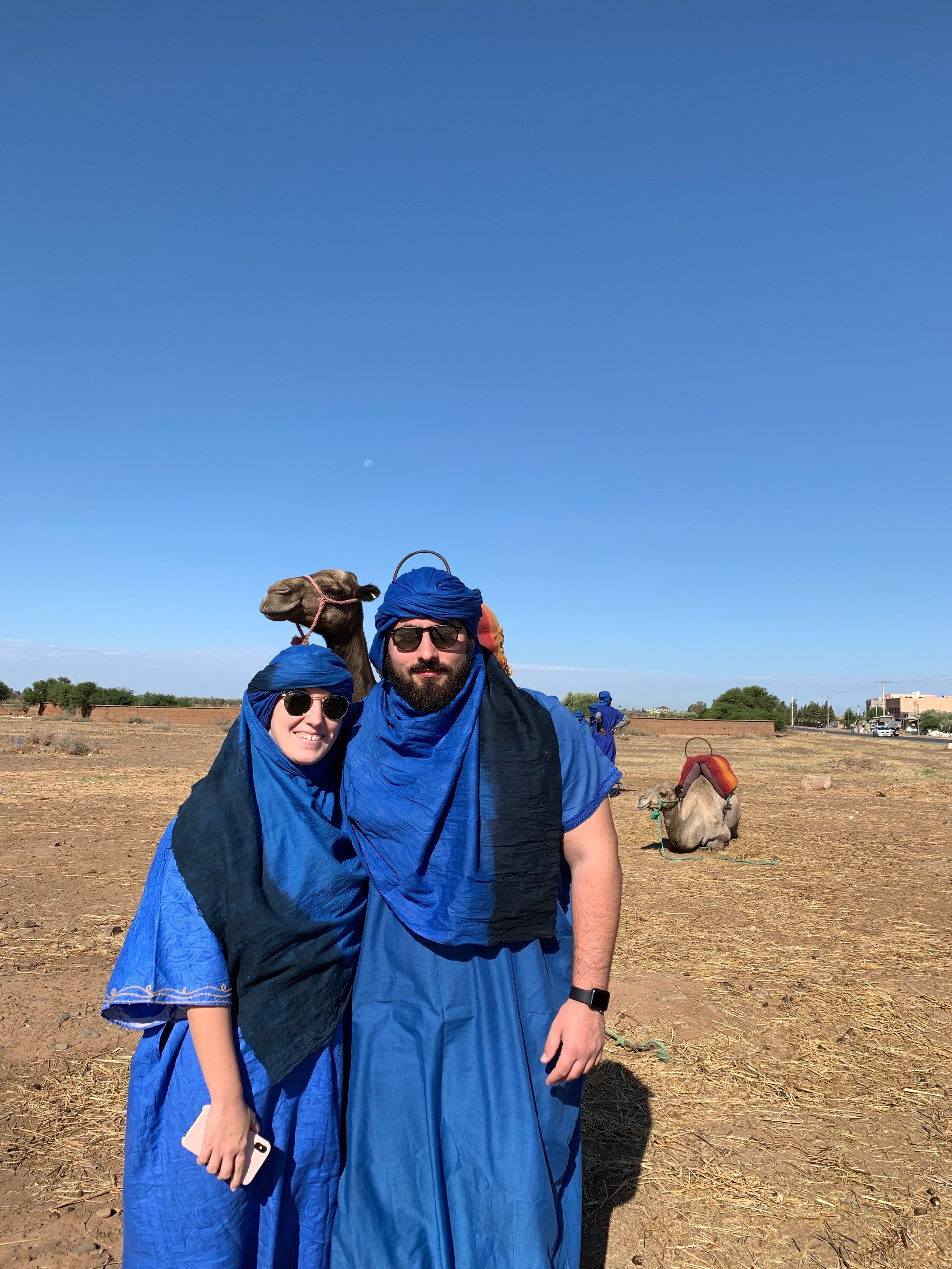 Portrait of man and woman in traditional clothes while standing in desert
