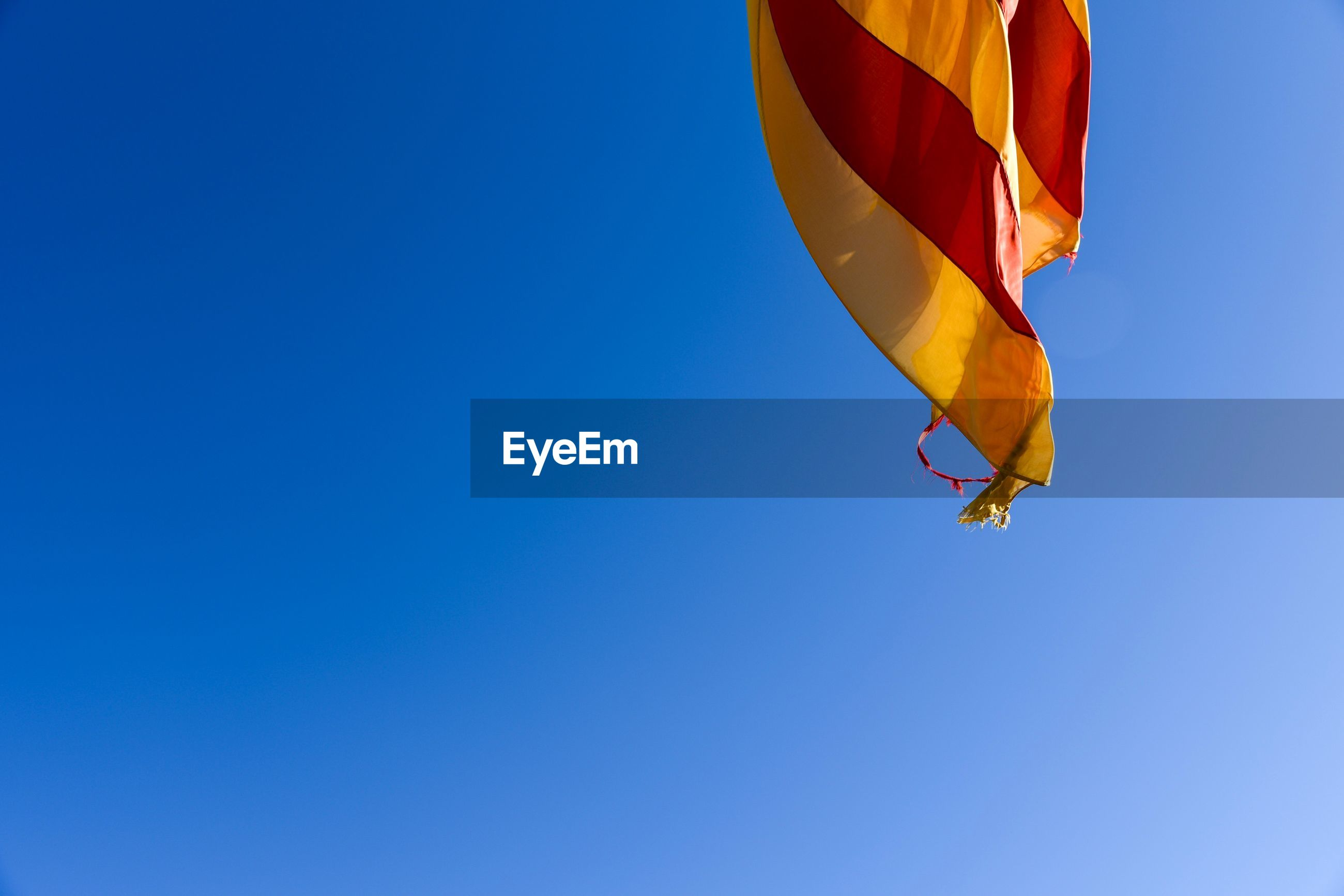 Low angle view of catalunya flag against clear blue sky