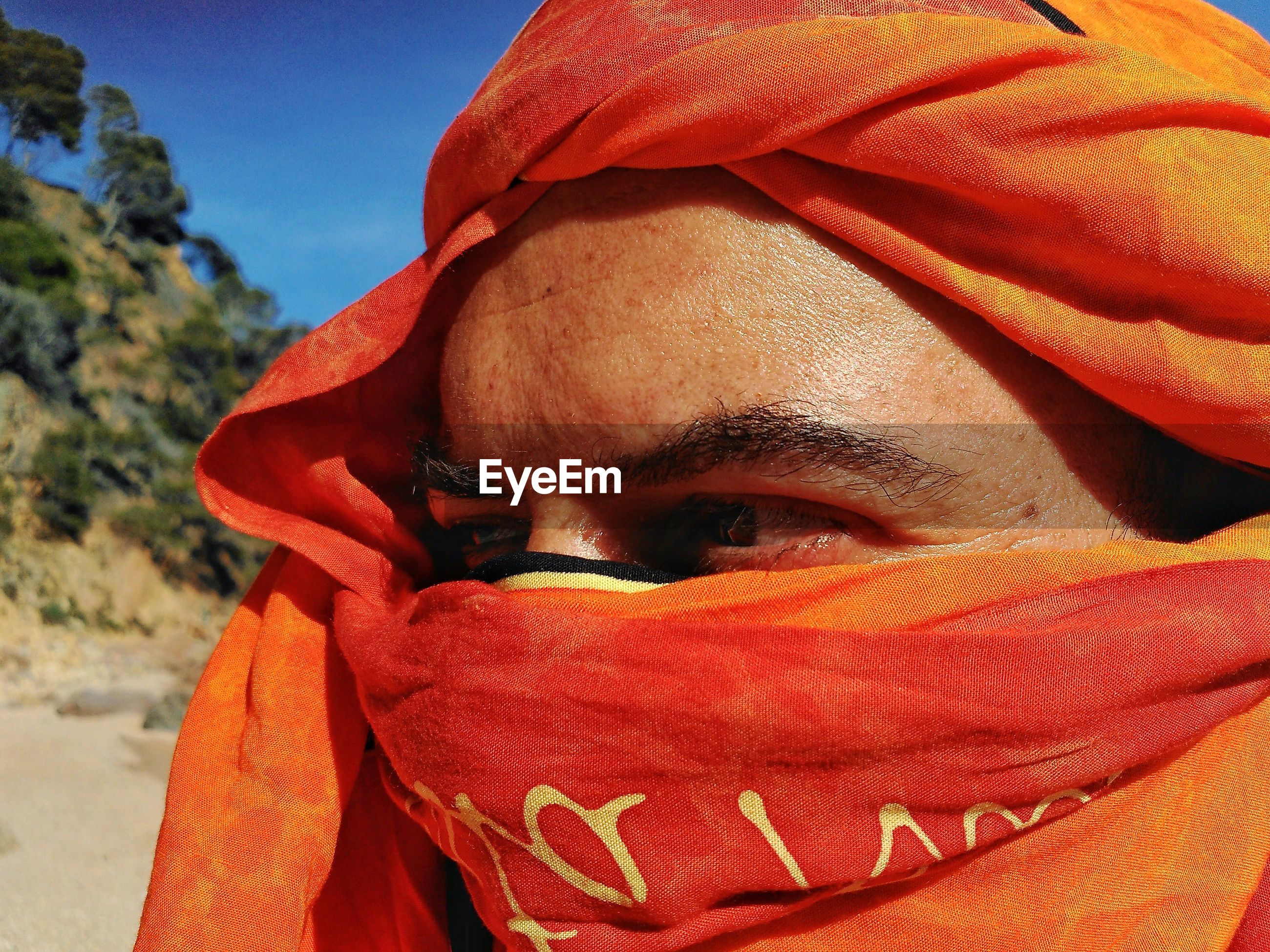 Close-up of man with face wrapped in textile during sunny day