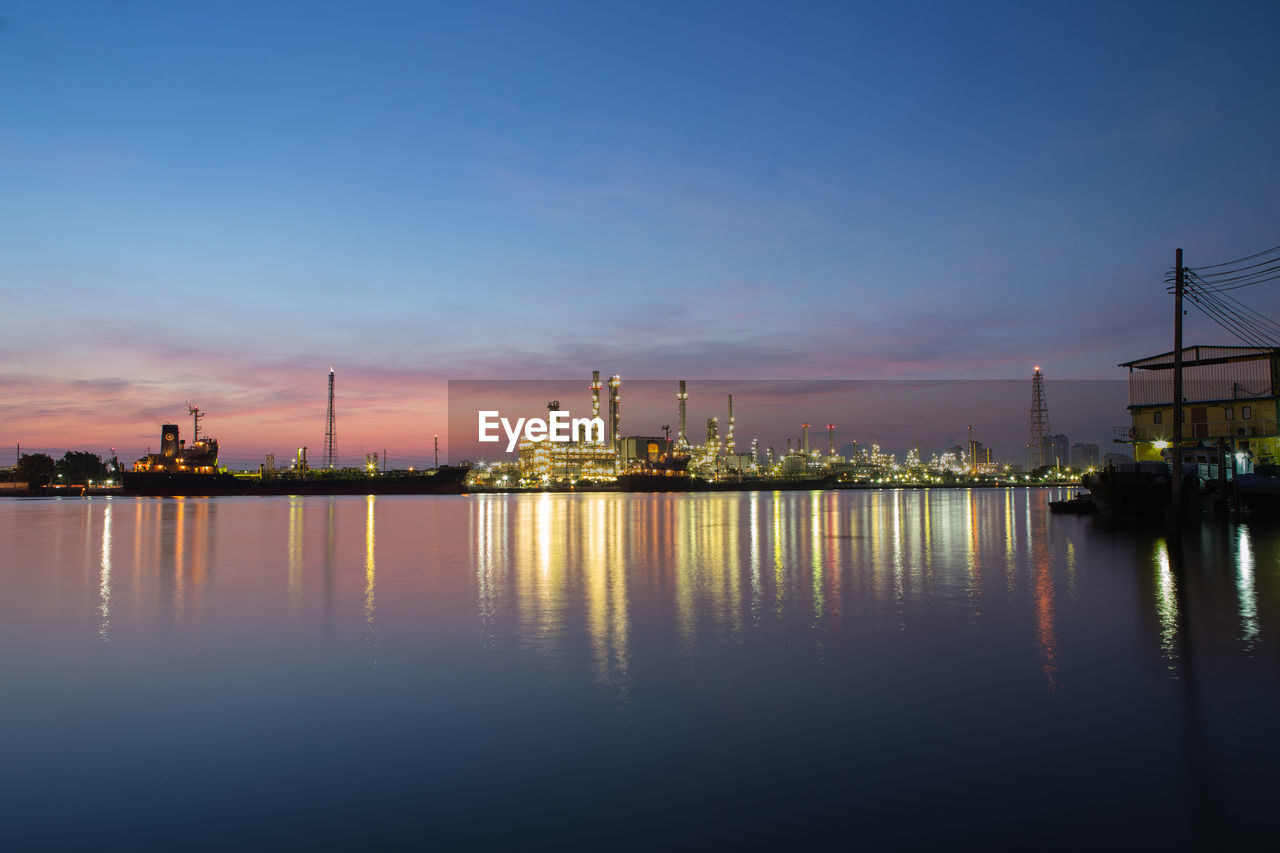 Illuminated Factory By River Against Sky At Dusk