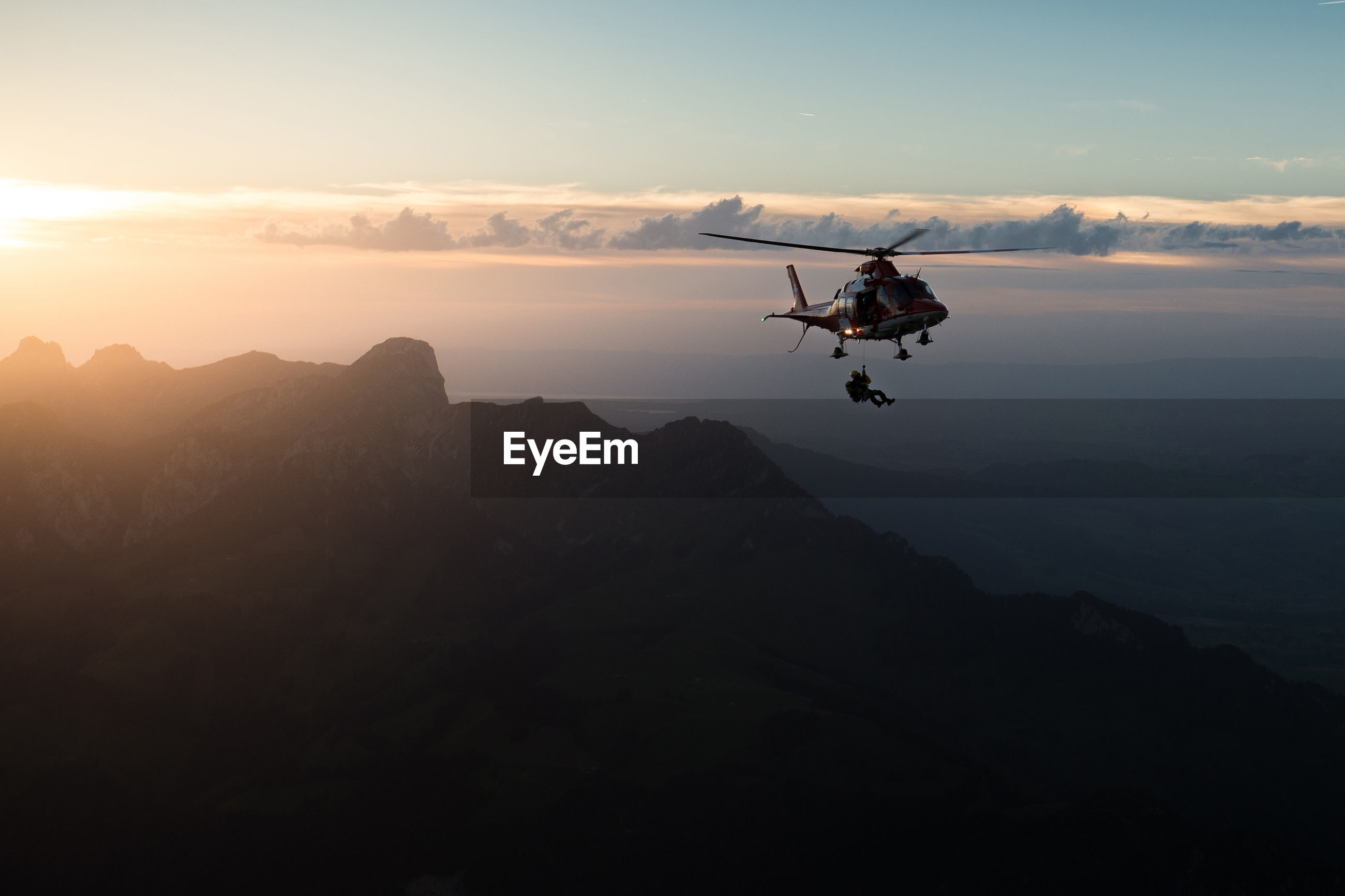 Man jumping from helicopter against sky