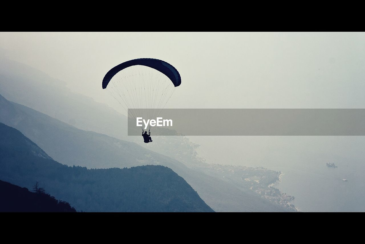 Silhouette person paragliding against mountains