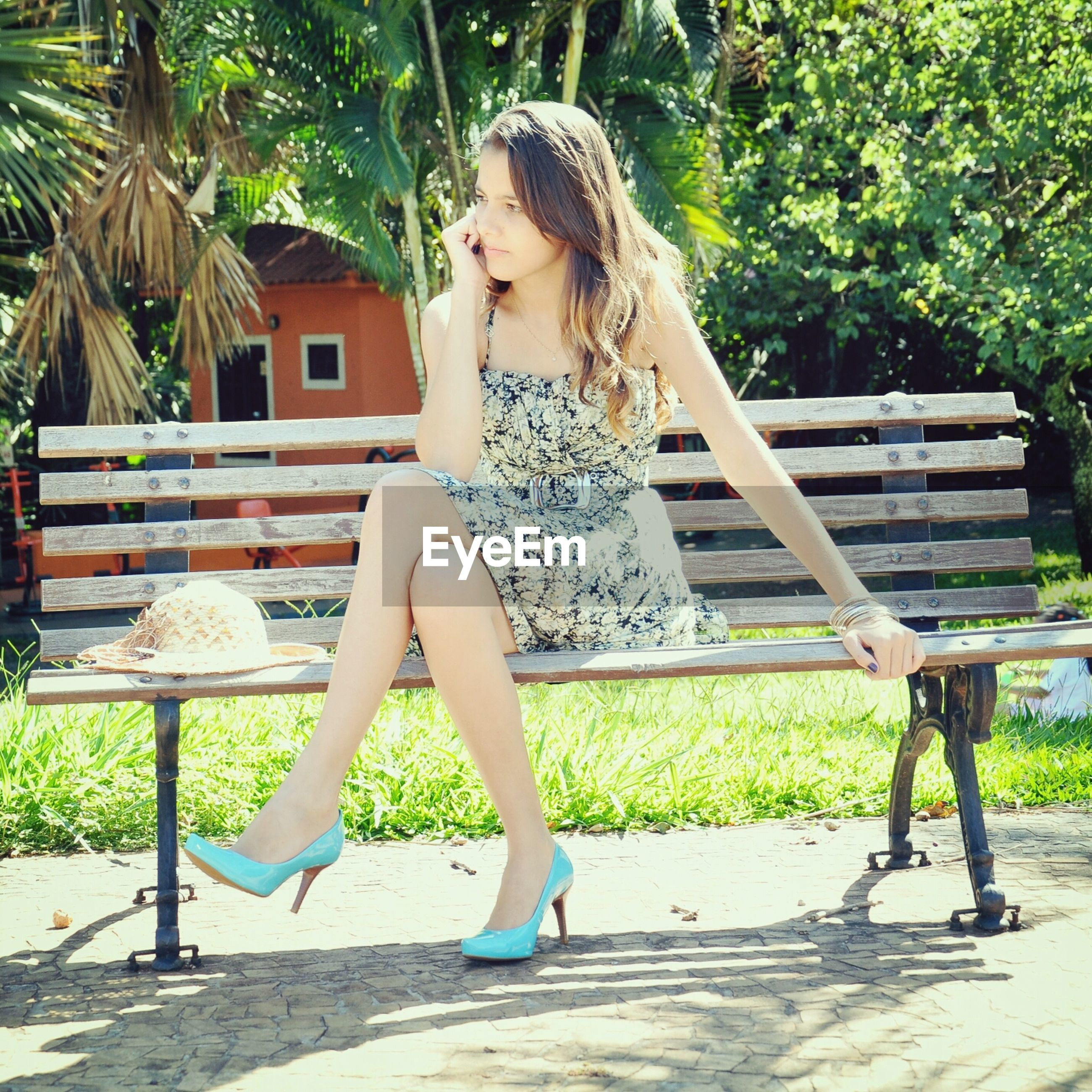 young adult, lifestyles, full length, person, young women, leisure activity, tree, casual clothing, sitting, relaxation, long hair, park - man made space, sunlight, standing, front view, dress, bench