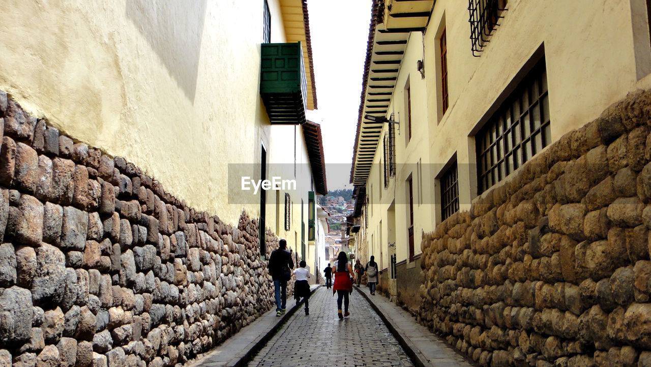 architecture, built structure, building exterior, building, two people, rear view, walking, men, the way forward, direction, women, adult, real people, wall, city, alley, people, day, full length, togetherness, stone wall, outdoors, couple - relationship