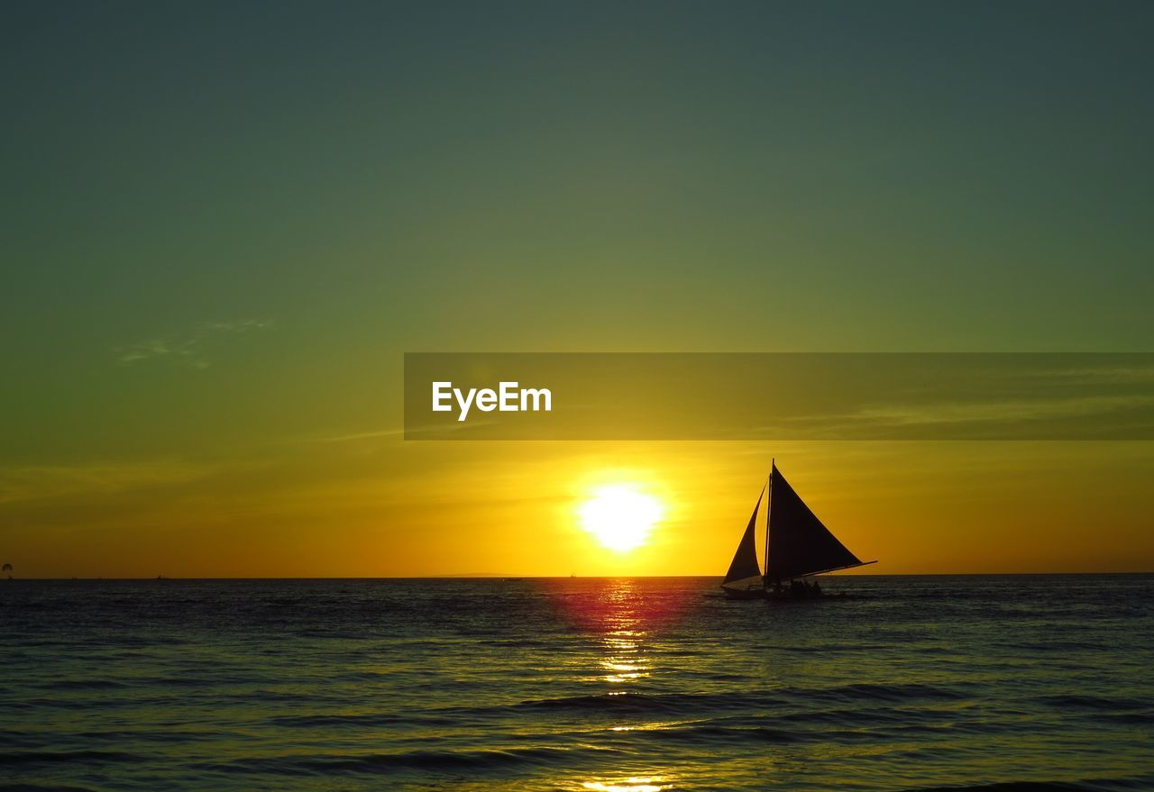 sunset, beauty in nature, water, scenics, sea, tranquility, nature, orange color, tranquil scene, sky, horizon over water, idyllic, silhouette, sun, nautical vessel, no people, reflection, waterfront, outdoors, sailing, yellow, sailboat