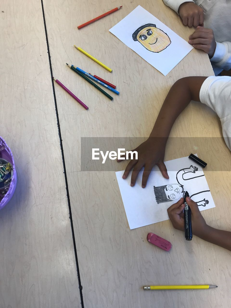 Midsection Of Children Making Drawing On Table