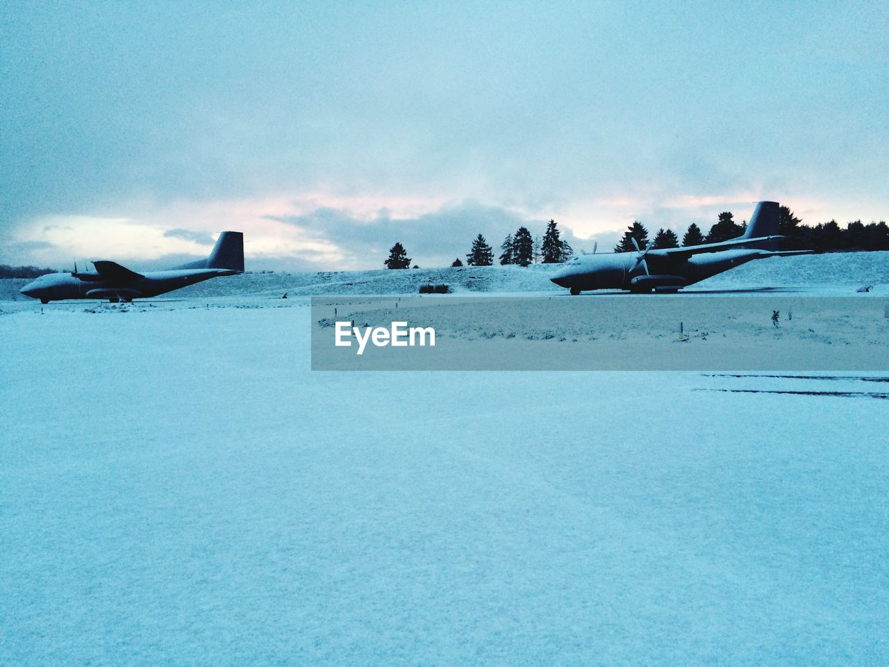 Airplanes On Snowy Airport Runway Against Cloudy Sky At Dusk