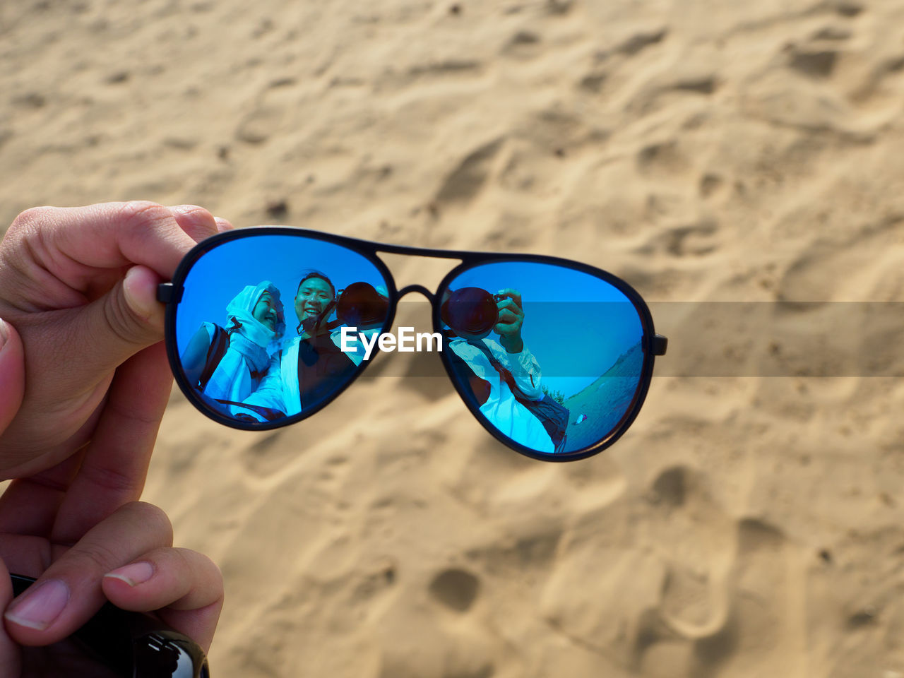 Close-Up Of Hand Holding Sunglasses At Beach