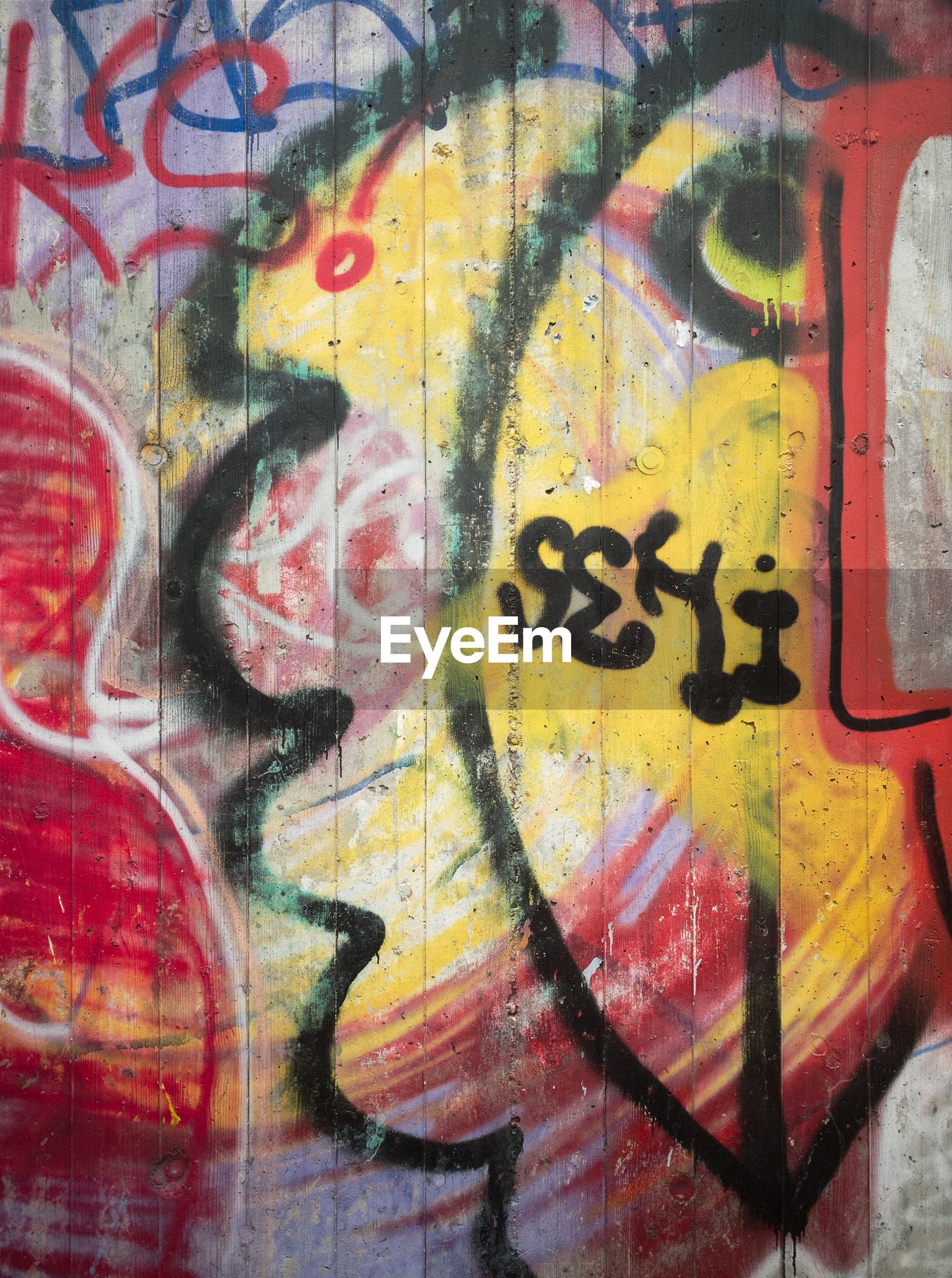 FULL FRAME SHOT OF MULTI COLORED GRAFFITI ON WALL