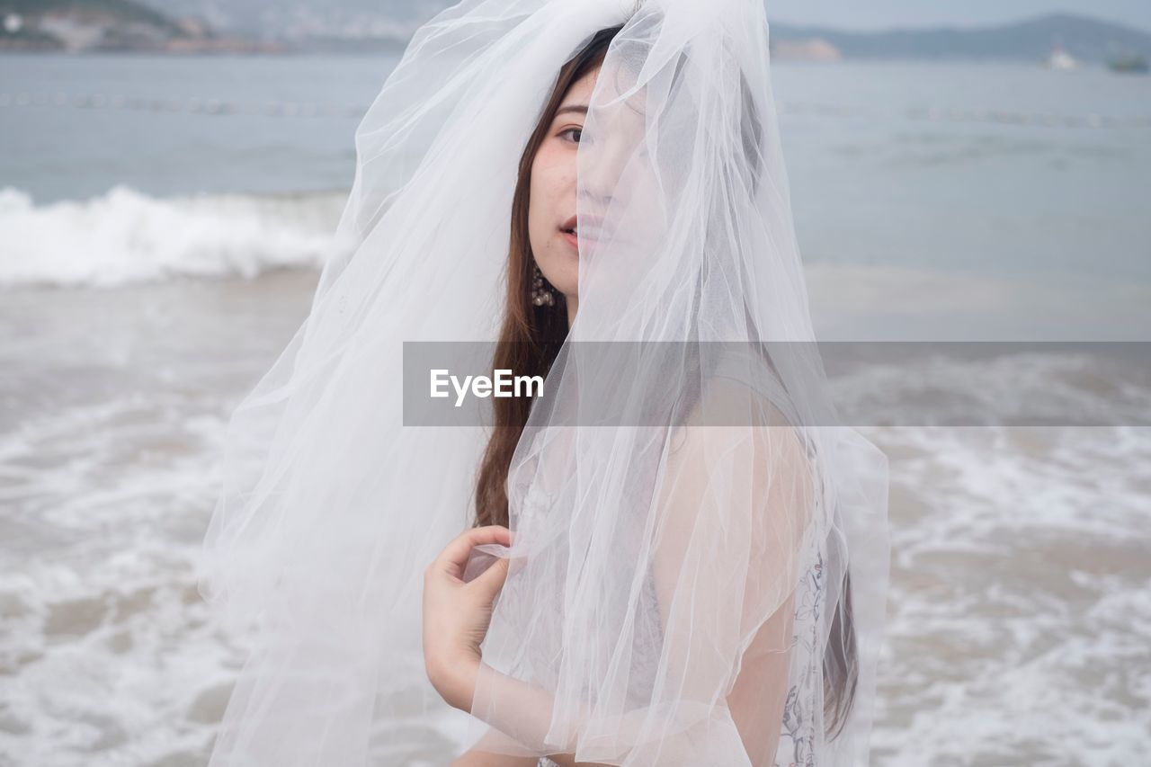 Portrait Of Bride Wearing Veil Standing At Beach