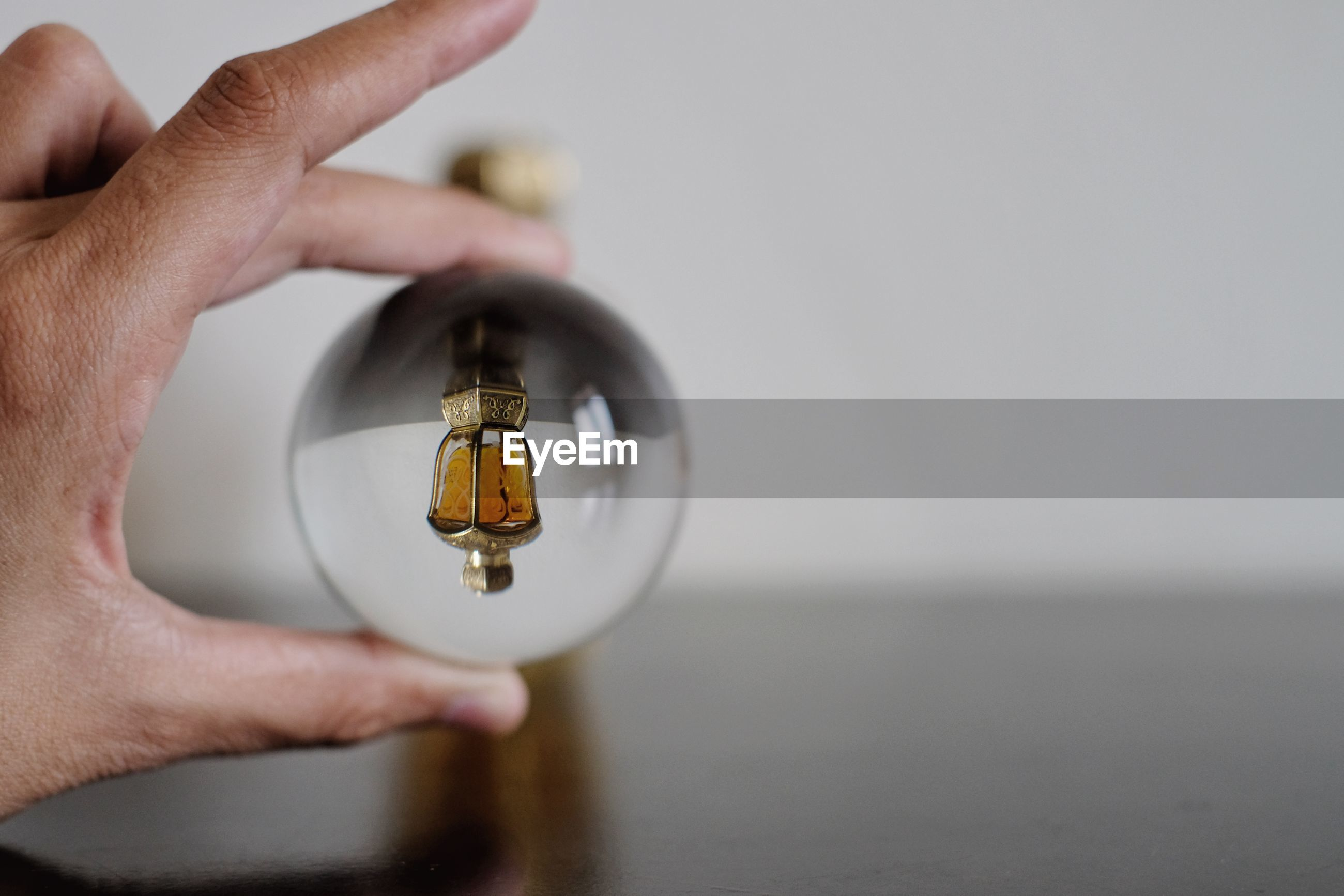 Upside down image of perfume bottle reflecting in crystal ball held by hand