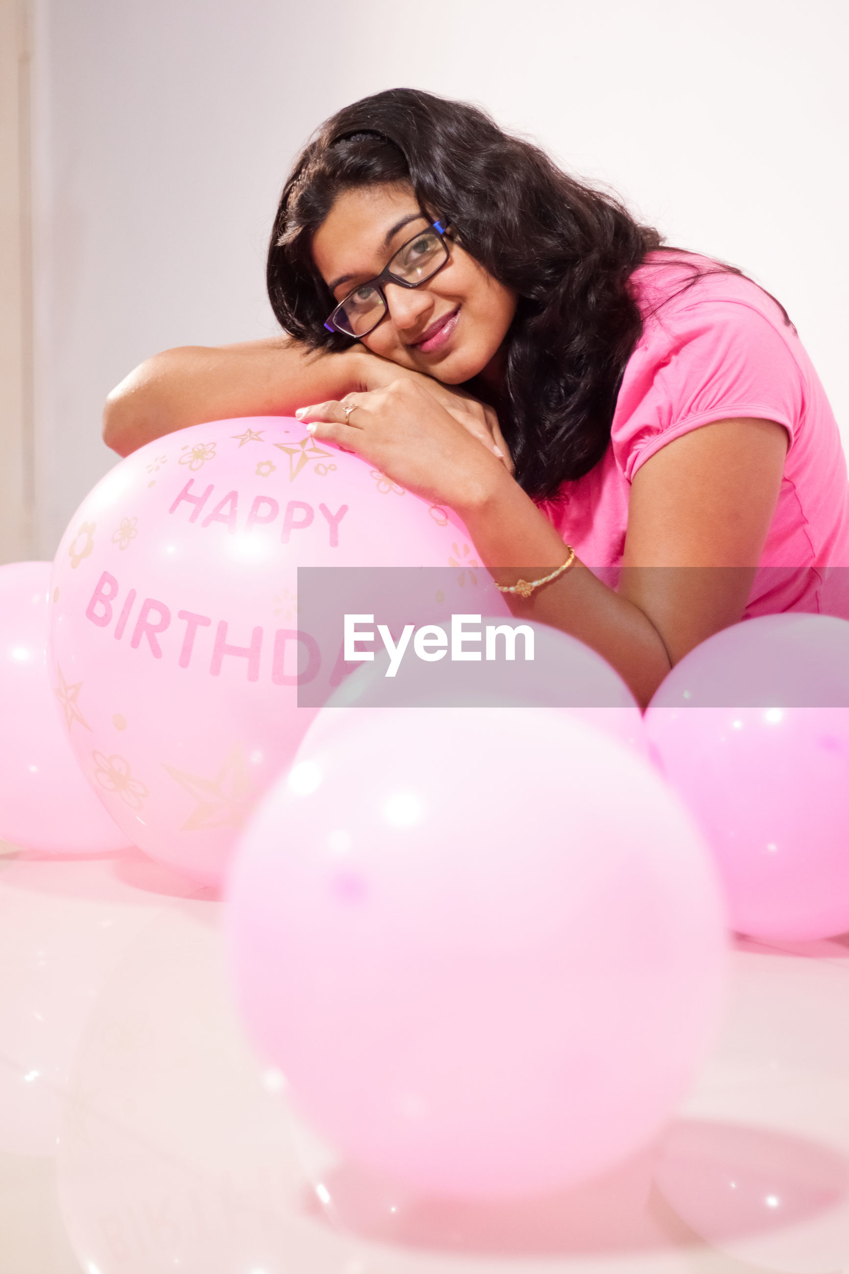 Portrait of smiling woman with pink balloons at home