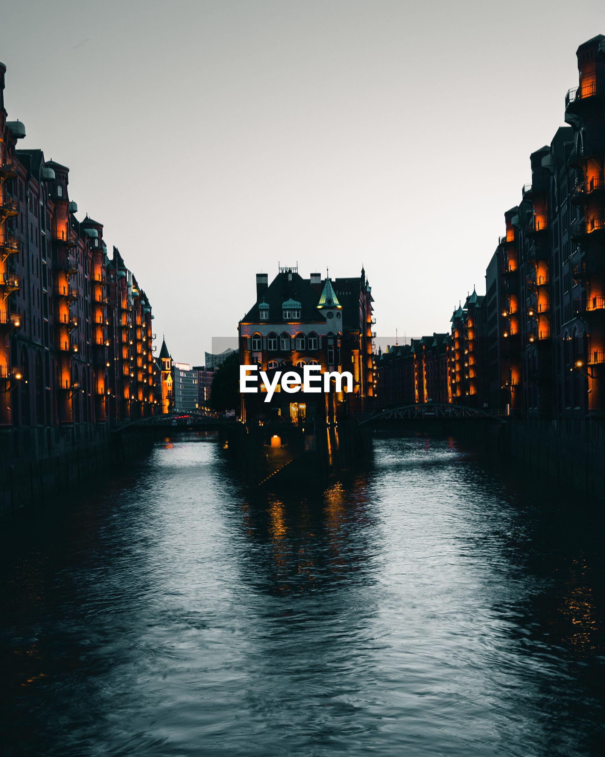 River amidst illuminated buildings against clear sky at dusk