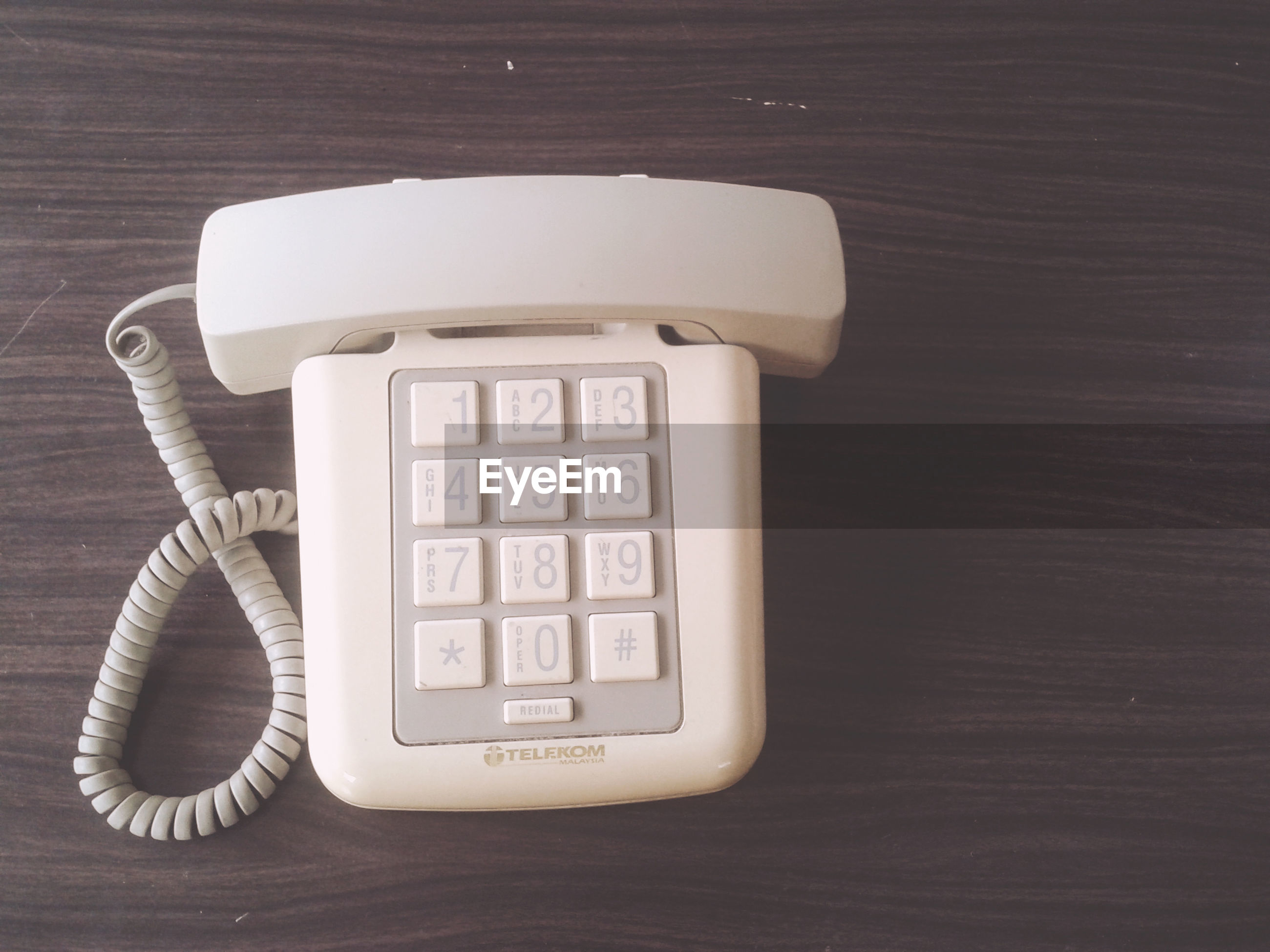 indoors, technology, communication, still life, table, close-up, connection, old-fashioned, single object, wood - material, high angle view, number, retro styled, no people, telephone, text, wireless technology, wall - building feature, western script, antique