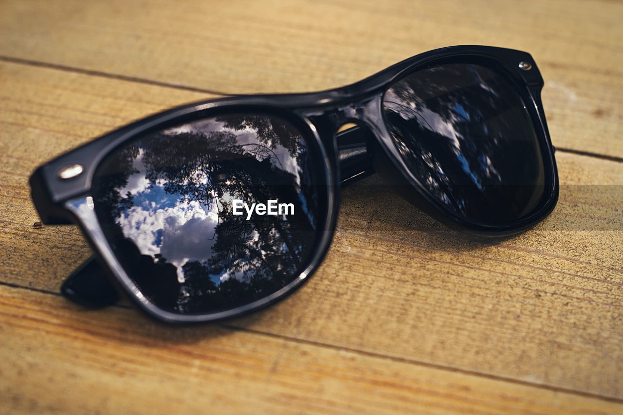 HIGH ANGLE VIEW OF SUNGLASSES WITH REFLECTION ON TABLE