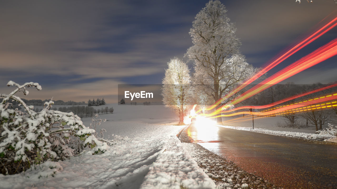 LIGHT TRAILS ON SNOW COVERED ROAD AGAINST SKY DURING SUNSET