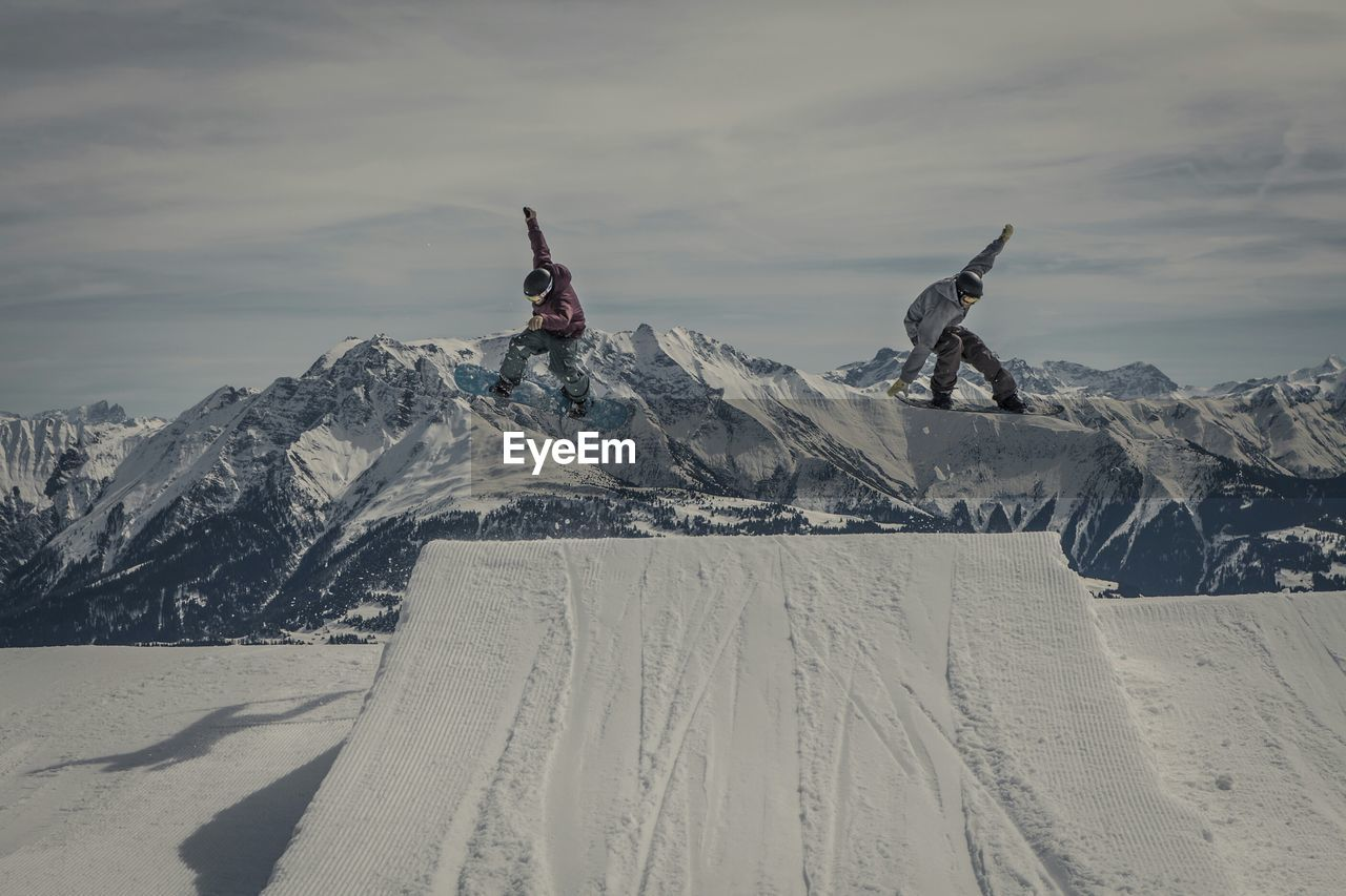 Snowboarders Jumping Over Snow Covered Ramp At Mountains Against Sky
