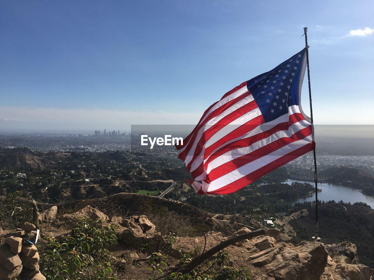 American flag on landscape against sky