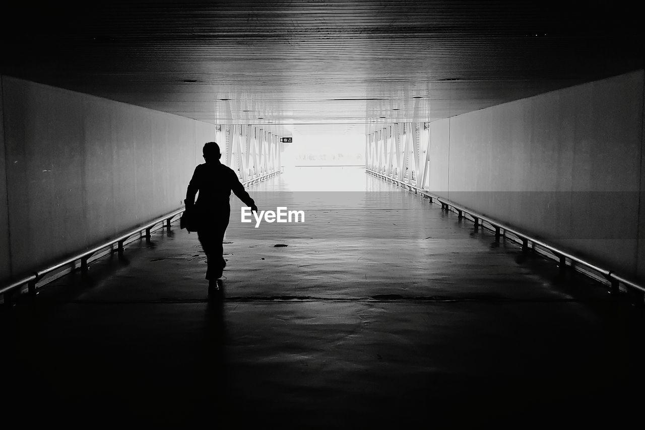 Full Length Of Silhouette Man Walking In Tunnel