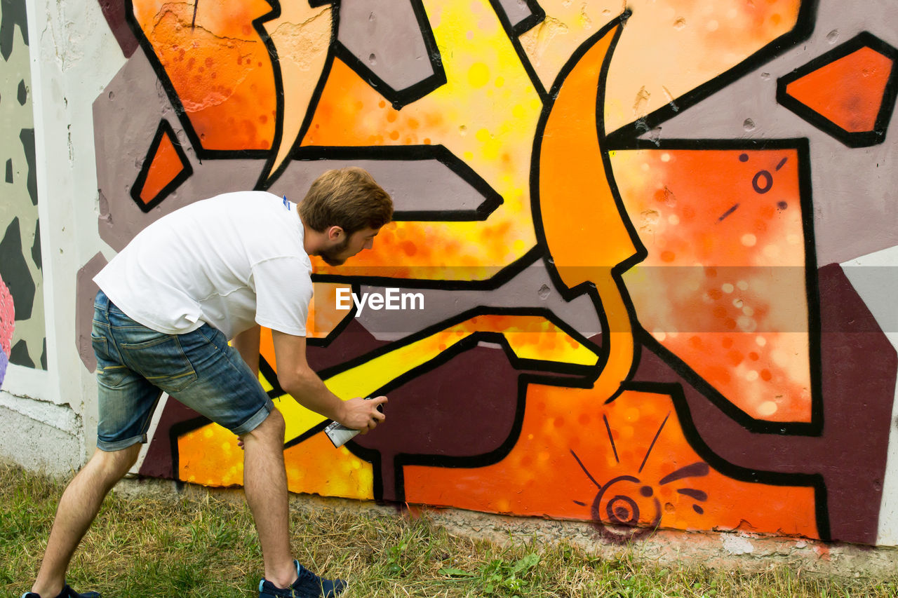 graffiti, men, one person, real people, full length, wall - building feature, males, casual clothing, art and craft, lifestyles, side view, creativity, boys, leisure activity, architecture, day, child, holding