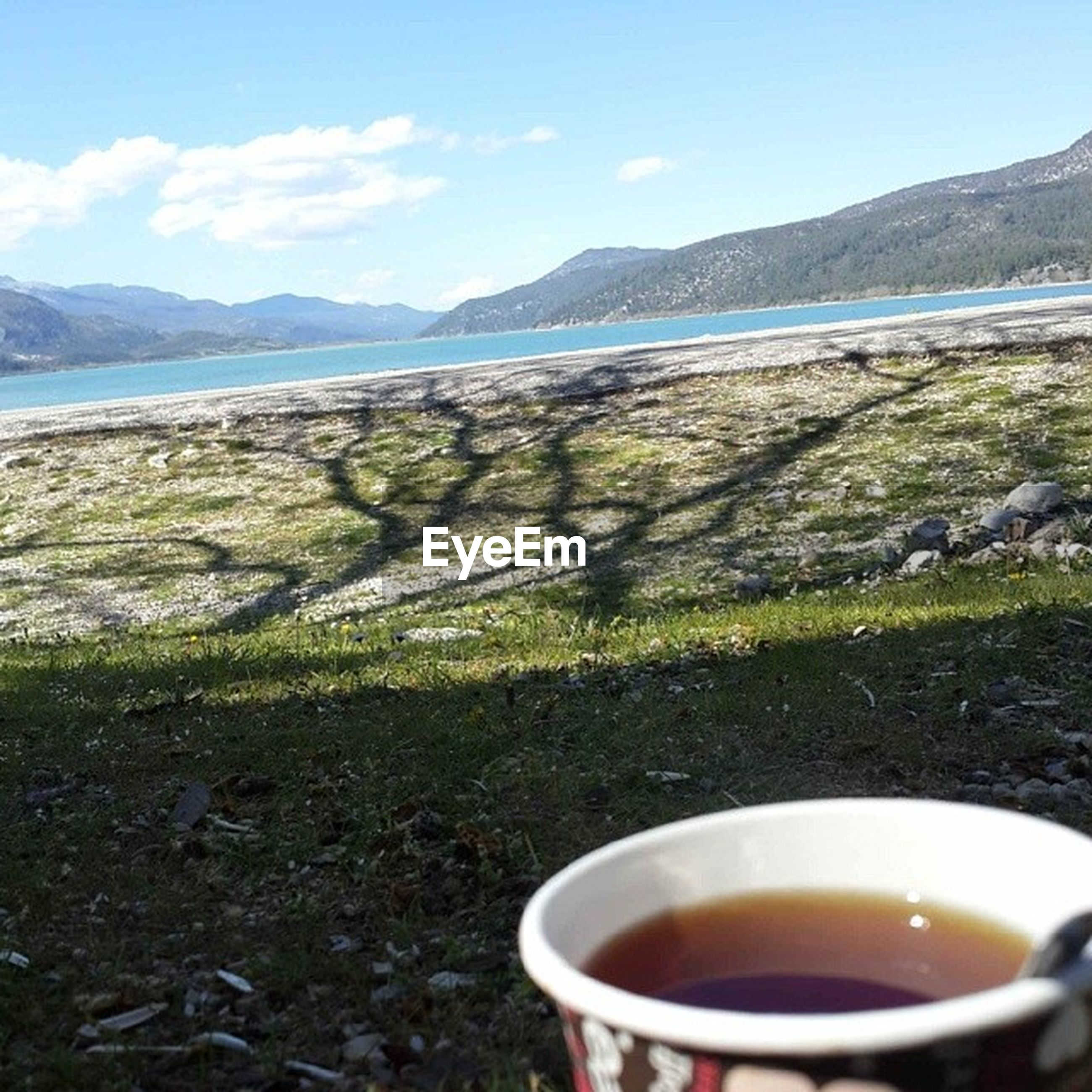 mountain, sky, tranquil scene, tranquility, drink, scenics, food and drink, beauty in nature, coffee cup, landscape, mountain range, nature, refreshment, close-up, water, table, cloud, day, idyllic, no people