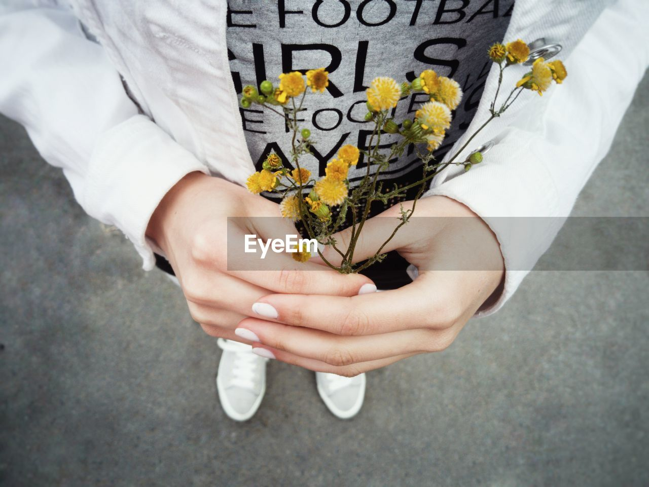 Low section of man holding yellow flowers on street