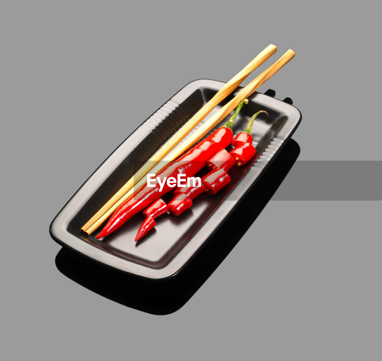 Red chili peppers with chopsticks in tray on gray background