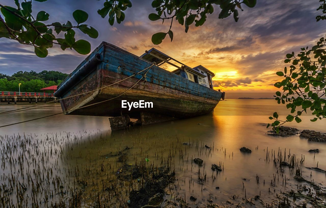 water, sky, nautical vessel, transportation, mode of transportation, cloud - sky, nature, tranquility, sunset, scenics - nature, tranquil scene, no people, plant, sea, beauty in nature, reflection, moored, tree, travel, outdoors, fishing boat