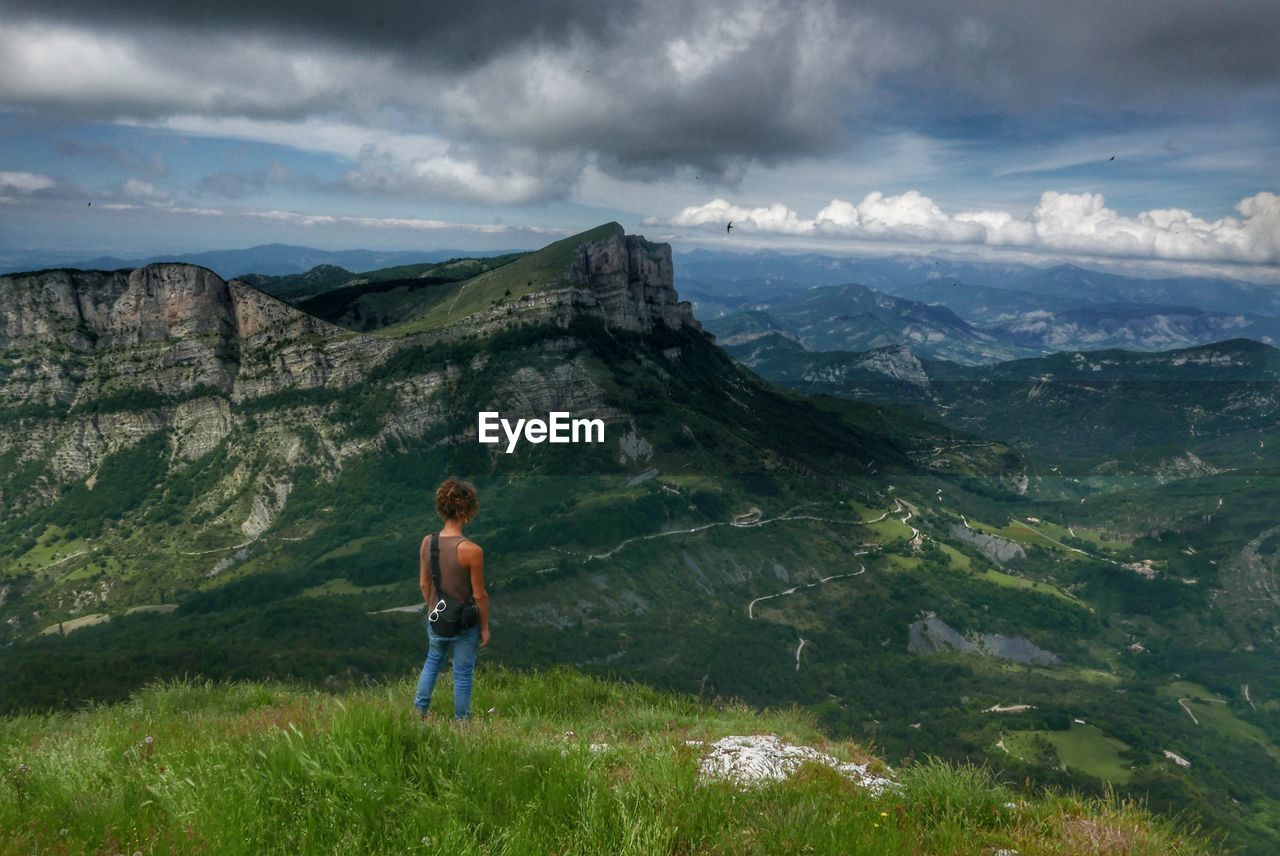 mountain, sky, cloud - sky, one person, real people, nature, standing, mountain range, day, casual clothing, beauty in nature, full length, outdoors, leisure activity, landscape, scenics, grass, adventure, lifestyles, young adult, adult, people